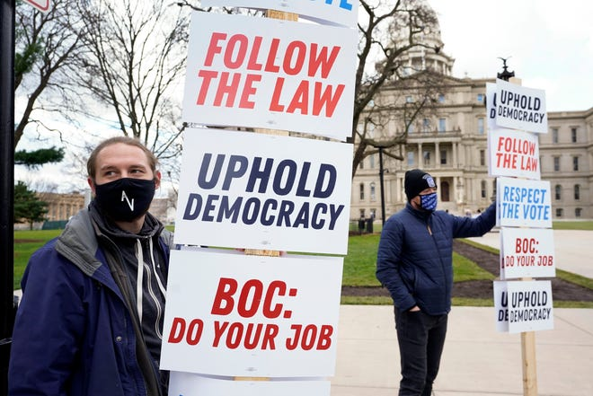 Joscha Weese, left, stands outside the Capitol building during a rally in Lansing, Mich., on Saturday. Michigan election officials on Monday certified Democrat Joe Biden's 154,000-vote victory in the state amid President Donald Trump's brazen attempts to subvert the results of the election.