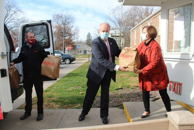 Left to right: Hy-Vee employee Adam Smutzer, Macomb Mayor Mike Inman and Representative Norine Hammond form a chain to deliver Thanksgiving meal kits to the Salvation Army in Macomb.