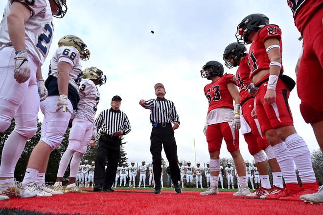 Head referee Ron Sudmyer makes the opening coin toss as former captains watch before the annual Wellesley and Needham Thanksgiving Day football game last year. The matchup is the oldest public high school football rivalry game in the country in a series that began in 1882. The two teams won't get a chance to play this Thanksgiving due to the ongoing coronavirus pandemic.