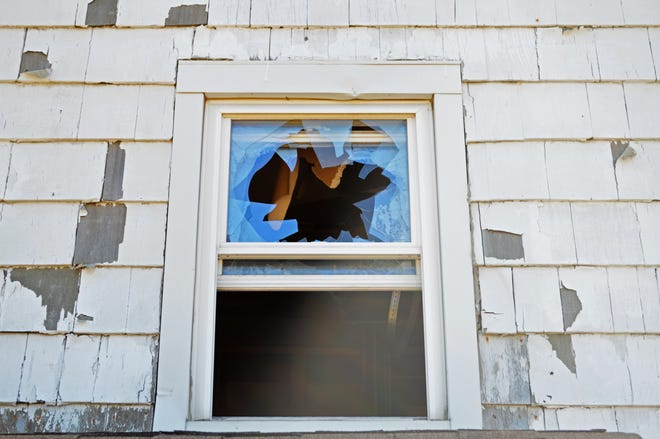 A broken window on 119 Leland Street in Framingham. The family that lived in the house was forced to leave when it was polluted by chemicals from nearby hazardous waste management company General Chemical, which is now closed.