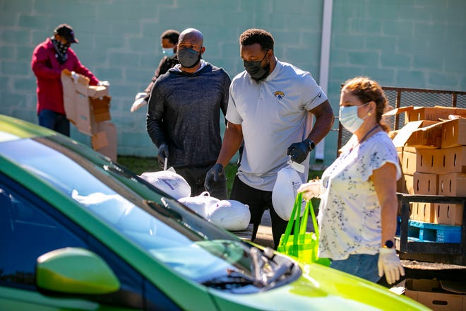 Retired NFL player Drayton Florence, left, and current NFL player Lerentee McCray, right, work on Monday at a special pre-Thanksgiving event to benefit Ocala Housing Authority residents. The giveaway featured turkeys, groceries and Publix gift cards.