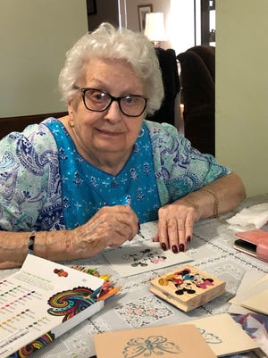 Miriam Campo's mother Hortensia Alam helps color some of the cards that are being created for residents of The Atrium assisted living facility in Boca Raton.
