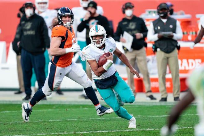 Dolphins quarterback Tua Tagovailoa (1) runs the ball in the third quarter against the Denver Broncos on Nov. 22