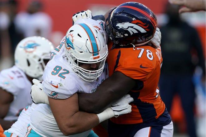 Miami Dolphins defensive end Zach Sieler (92) battles Denver Broncos offensive tackle Demar Dotson (78) on Sunday. (AP Photo/Jack Dempsey)