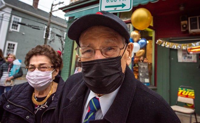 Manuel Pedroso, com a sua esposa Maria Pedroso, acena para a caravana de carros decorados, realizada no domingo passado, para comemorar o seu 101º aniversário, em frente ao seu esta-belecimento comercial Friends Market, na Brook Street, em Providence.