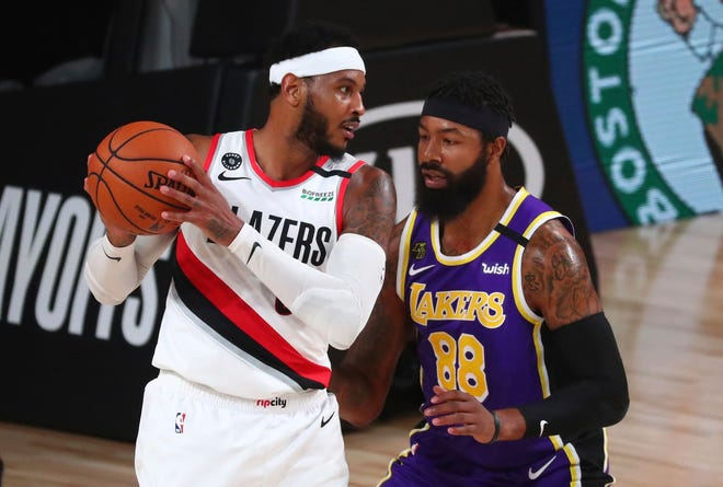 Portland Trail Blazers forward Carmelo Anthony, left, controls the ball against Los Angeles Lakers forward Markieff Morris (88) in the first half of Game 3 of an NBA basketball first-round playoff series in August. (Kim Klement/Pool Photo via AP)