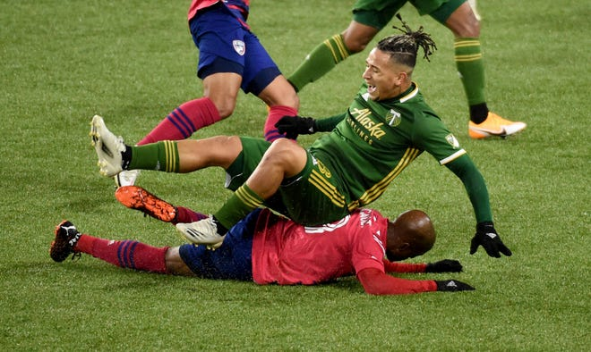 FC Dallas forward Fafa Picault, bottom, slide tackles Portland Timbers defender Pablo Bonilla, top, during the first half of an MLS soccer match in Portland on Sunday. (AP Photo/Steve Dykes)