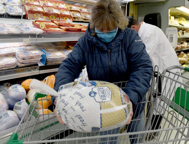 Alice Springer of North Canton picks up a turkey Monday at the Fishers Foods in Jackson Township. With the rising cases of COVID, many people are opting to forgo large traditional gatherings with family and friends.