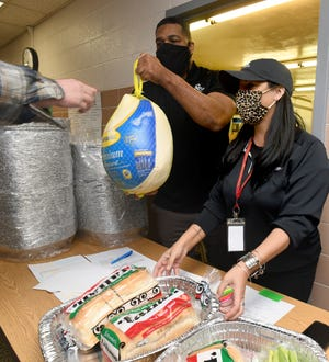 Joe Turner and Melissa Printz of Arrow Passage Recovery pass out turkeys they donated for the Massillon City Schools' Turkeys for Tigers program.