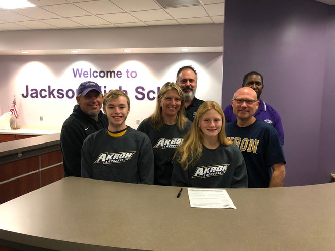 Joining Jackson's Hannah Sanders when she signed her letter of intent to play women's lacrosse at Akron were (front row) assistant coach Mahlon Downard, her boyfriend Bailey Young, her mother Danielle Sanders, her father Jeff Sanders, (back row) head coach John Kroah and assistant coach Mike Peterson. (Photo courtesy of Jackson High School)