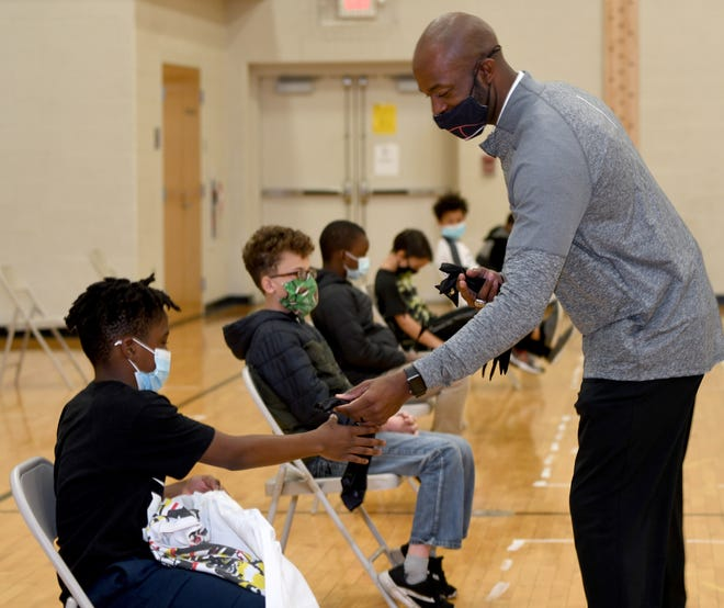 Devin Jordan from Beyond the Game Organization, passing a tie to fifth grade student Derrick Gordan, has brought the Guys with Ties program to Gibbs Elementary in Canton. The boys got their shirts and ties at the inaugural meeting at the school Monday.
