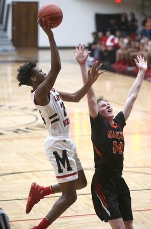 McKiney's James McCollough (left) drives to the basket while being guarded by Green's Zack Oddo during the first quarter of their game at McKinley on Friday, Dec. 20, 2019. (CantonRep.com / Scott Heckel)