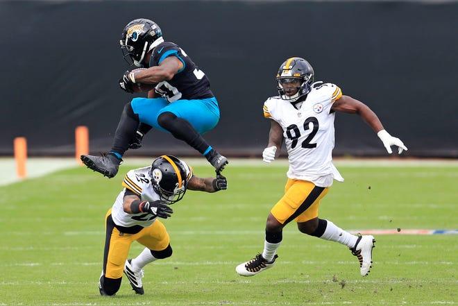 Jacksonville Jaguars running back James Robinson leaps over Pittsburgh Steelers cornerback Steven Nelson (22) as linebacker Olasunkanmi Adeniyi (92) comes in to help Sunday, Nov. 22, 2020, in Jacksonville, Fla. MATT STAMEY/THE ASSOCIATED PRESS