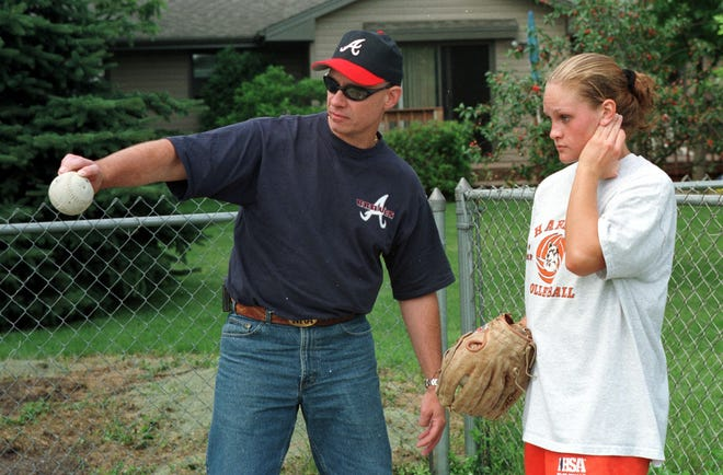 Longtime pitching coach Tim Parrish, shown in June 1999 working with Emily Granath during softball practice in her backyard, died Saturday from COVID-19.