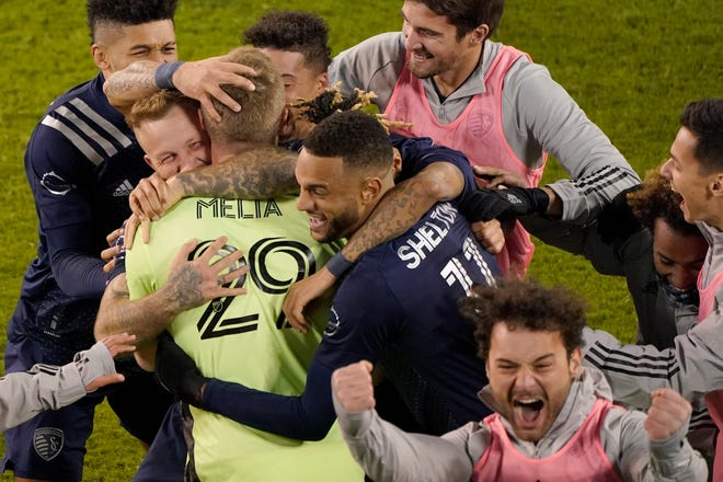 Sporting Kansas City players celebrate after winning an MLS soccer match against the San Jose Earthquakes with a penalty kick in overtime Sunday in Kansas City, Kan.