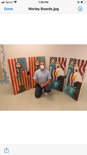 Nicholas Worley, an offender with the Kewanee Life Skills and Re-Entry Center, kneels in front of his recent art pieces he donated to a local fundraiser. Among Worley's community contributions is a pencil drawing of E.E. Baker (inset) that the artist gave to the Kewanee Park District for its 100th Anniversary. The framed art hangs in the KPD office building.