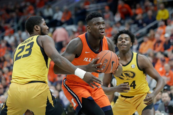 Illinois' Kofi Cockburn, center, heads to the basket past Missouri's Jeremiah Tilmon and Kobe Brown during the first half of an NCAA college basketball game in St. Louis on Dec. 21, 2019.