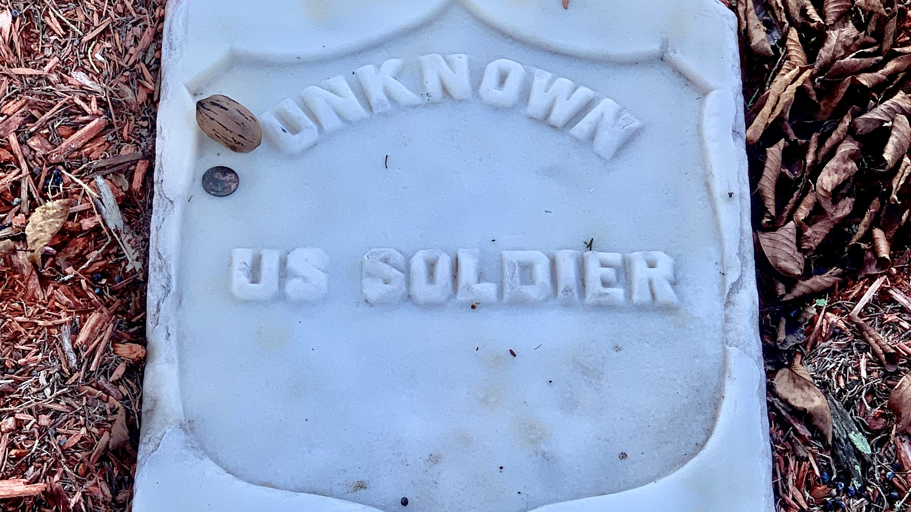 A pecan and a penny rest atop the grave of an unknown soldier at New Bern National Cemetery on Nov. 14.