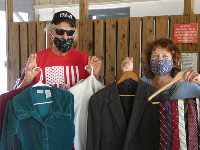 John and Georgie Jackson display some of the clothing items that were donated during the Yacht Club's highly successful drive. [CONTRIBUTED PHOTO]
