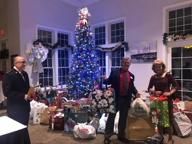 Linda Lelli poses by the gift-laden Christmas tree at last year's FHYC holiday party. All the gifts were delivered to the Salvation Army for their Angel Tree program. [CONTRIBUTED PHOTO]