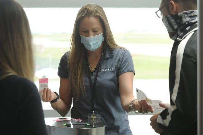 Station supervisor Cheryl Minkema checks passengers in at their Worcester Regional Airport gate before a flight July 2.