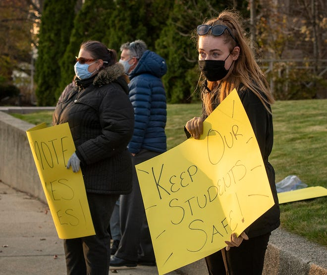 Second-grade teacher Brittany O'Neil and others protest Monday in front of the Diocese of Worcester offices on Elm Street, seeking a switch to remote learning after Thanksgiving break.