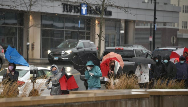 Likely eager to see family this week and hoping for a negative COVID-19 result, test-seekers stand in a long line in heavy rain outside the Mercantile Center in downtown Worcester on Monday.
