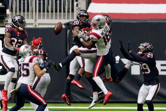 Houston strong safety Justin Reid breaks up a pass intended for New England wide receiver Jakobi Meyers during Sunday's game.