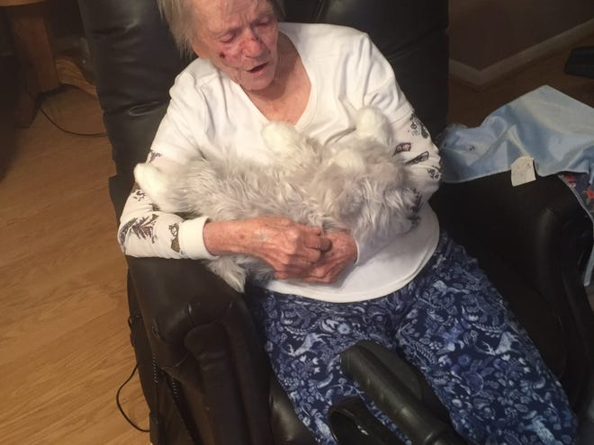 Myrtle Feagle, 87, cuddles Silver, her robotic cat. Silver is part of a state program that distributes the robotic pets to older adults with Alzheimer's disease and dementia to help offset social isolation. Feagle's daughter, Sylvia Rowell, says Silver has helped her mother immeasurably.