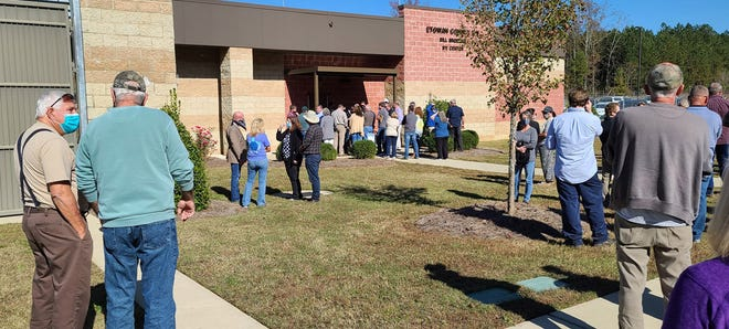 Opponents of a proposed animal feed ingredients plant in Gadsden are pictured Friday outside a meeting of the Gadsden Airport Authority, which owns the property where the plant would be located.