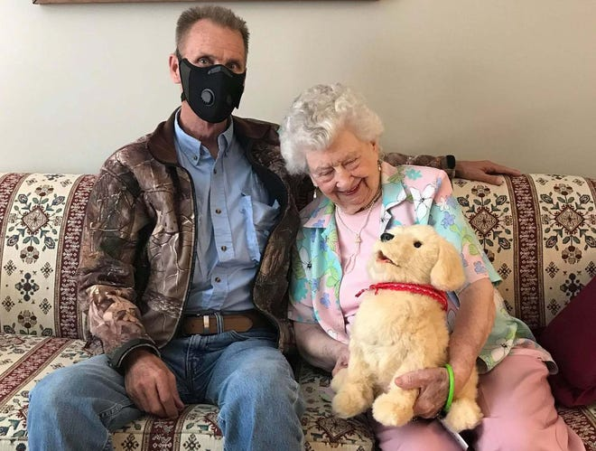Joe Nelson embraces his 93-year-old mother, Merle Nelson, at Mathison Retirement Center on Monday as she holds a robotic puppy. Joe Nelson is raising money to donate 20 robotic pets to the facility by Christmas in hopes to bring companionship to isolated elderly residents.