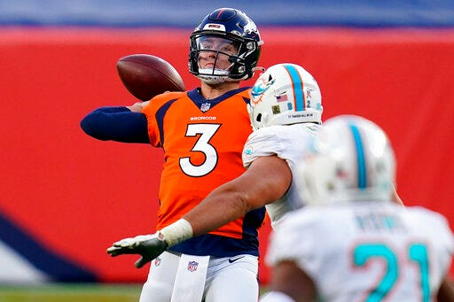 Denver Broncos quarterback Drew Lock, left, throws under pressure from Miami Dolphins defensive end Zach Sieler during the second half Sunday at Empower Field at Mile High in Denver. [AP photo/David Zalubowski]