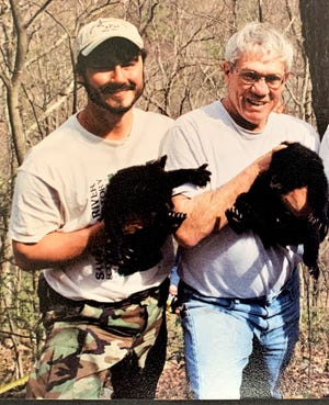 Andrew Bridges, left, and Whit Gibbons hold bear cubs that were part of a research study. The cubs were returned to their mother in the tree hollow. [Photo courtesy Andrew Bridges]