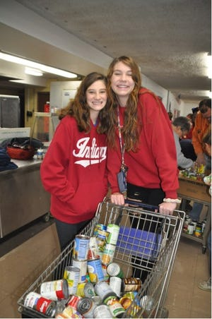 Morgan Geddes and Brooke Geddes help with the sorting for the White Christmas food drive that serves families in Grove City, Jackson Township, Urbancrest, Galloway, Harrisburg and Orient.