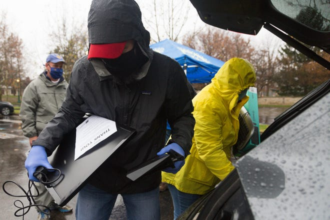 Eric Stoll (left) and Michele Hoyle remove computer parts from the back of a vehicle Nov. 21 at the Upper Arlington Municipal Services Center. The Rotary Club of Upper Arlington held a contactless computer-donation drive in partnership with the Central Ohio Broadband Access Pilot Program, which provides internet services and computers to central Ohio students for a nominal fee.