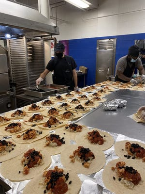 Kitchen staff at Lexington High School prepare burritos for students as part of the district's free meal program.