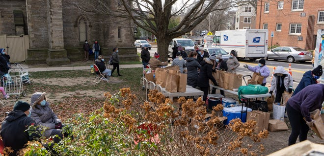 Unable to have as many people inside at one time, the Brookline Food Pantry now stages volunteers and clients outside St. Paul's Episcopal Church.