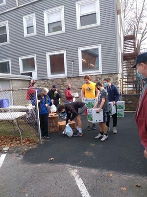 Saugus High School football players help deliver food to people at the Saugus United Parish Food Pantry Thanksgiving food drive