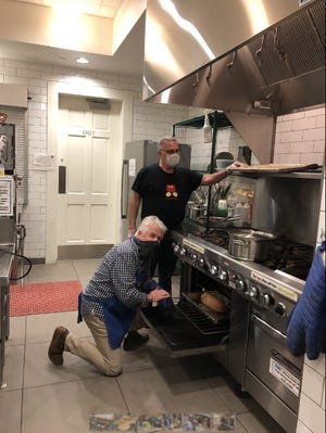 Volunteer chef Jim Murphy checks the temperature of a turkey in the Willcutt Commons kitchen while chef Dan Volungis oversees him.