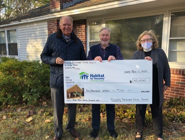 Trinity Episcopal Church Senior Warden Charlie Stone; Jay Luby, head of outreach; and Rev. Nancy J. Hagner present a check for $10,000 to Habitat for Humanity of Greater Lowell Nov. 4. Construction will begin soon on a Main Street home in West Concord.