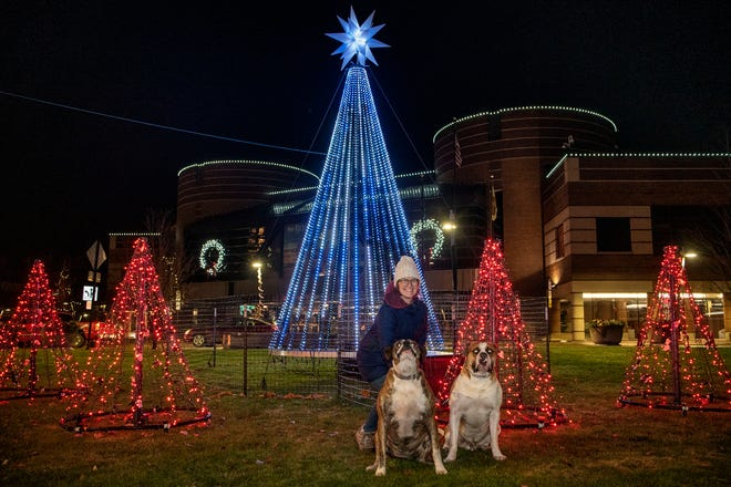 Alyssa Jones and her dog Reign and Gunner pose for a picture by the Christmas Tree at Mill Race Park on Sunday, Nov. 22, 2020 in Battle Creek, Mich.