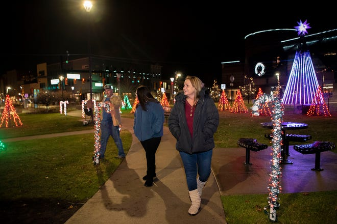 From left: Jim McQuiston, Destiny McQuiston and Joanie McQuiston scope out the International Festival of Lights on Sunday, Nov. 22, 2020 at Mill Race Park in Battle Creek, Mich.