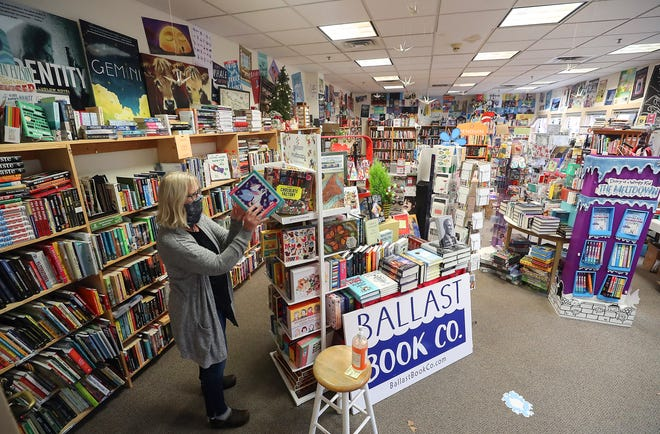 Suzanne Droppert organizes a display of puzzles while stocking the shelves in her Ballast Book Co. store in downtown Bremerton Monday, Nov. 23, 2020.