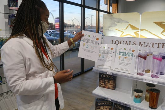 Pharmacist T'Bony Jewell shows off a children's science book by a local author for sale at her local Clarksville pharmacy, Zoren Pharmacy & Gifts, on Nov. 19, 2020.