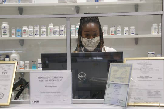 Pharmacist T'Bony Jewell works behind the counter at her local Clarksville pharmacy, Zoren Pharmacy & Gifts, on Nov. 19, 2020.