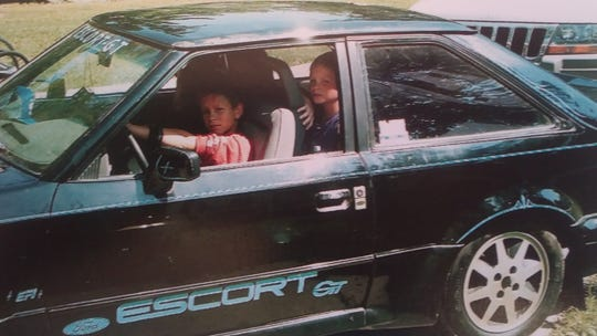 Derick Wallace, age 7, with his cousin Cody Schuckman, age 5, in the backseat of the Wallace family's beloved 1986 Ford Escort GT in 1999. Cody left dents on the hood and rooftop from dancing and the family kept them as memories.