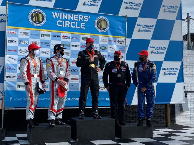 Ford CEO Jim Farley, middle, stands atop the winner's podium Sunday at the 2020 SVRA Road Atlanta Grand Prix, driving his classic Lola T298.