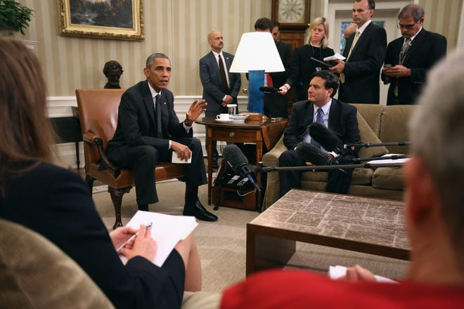 President Barack Obama (L) talks with reporters after a meeting with Ebola Response Coordinator Ron Klain (R) and other health and security advisors in the Oval Office at the White House October 22, 2014 in Washington, D.C.