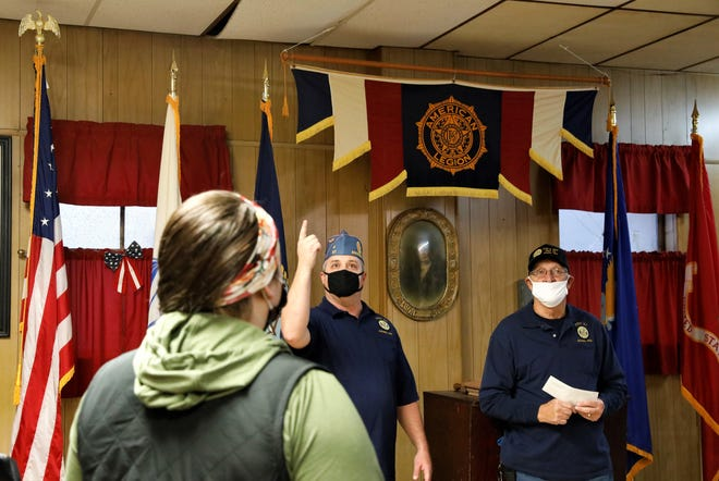 Issac Hill, center, indicates water damage to the ceiling of American Legion Post 57 in Amanda on Sunday, Nov. 22. Issac, the Squadron Commander of the Sons of the Legion and his father Eugene Hill, the post commander, pictured right, accepted donations from the Amanda Business Council to repair the roof of the post.