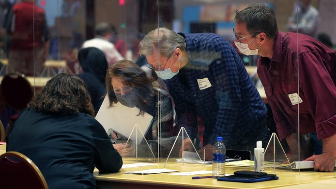 A pair of observers working on behalf of the Trump campaign, right, speak with election workers sorting through ballots cast in Dane County at the Monona Terrace Community and Convention Center in Madison on Monday. The Trump presidential campaign paid $3 million to the state to launch a recount only in Milwaukee and Dane counties, the state's two largest and most liberal. The effort, which is unlikely to overcome Biden's more than 20,600-vote lead, is seen by legal observers as preparation for a lawsuit.